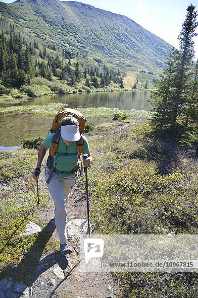 Woman backpacker hikes along Upper Fuller Lake in the Kenai National Wildlife Refuge on the Kenai Peninsula in South-central Alaska