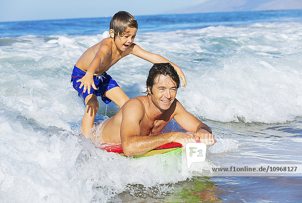 Father and Son Surfing Tandem Together Catching Ocean Wave  Carefree happy fun smiling lifestyle