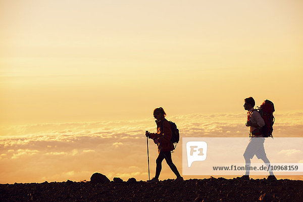 Hikers with backpacks hiking on top of a mountain at sunset