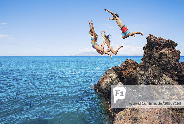 Summer fun  Friends cliff jumping into the ocean.