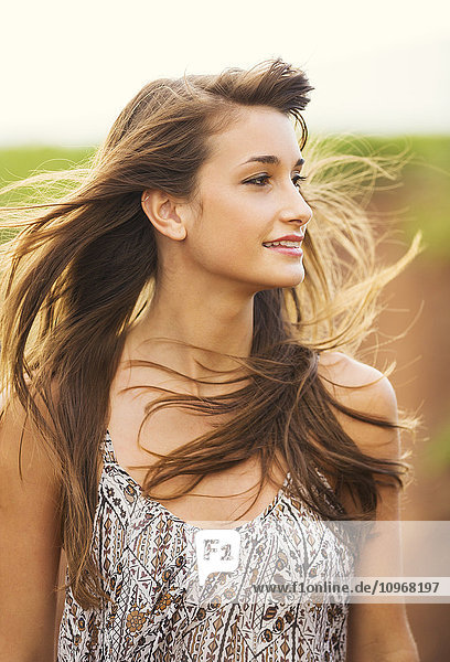 Gorgeous Romantic Girl Outdoors. Beautiful Model in Short Dress in Field. Long Hair Blowing in the Wind. Backlit  Warm Color Tones