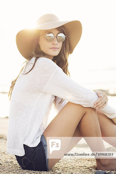 Fashion portrait of beautiful young woman wearing sunglasses and hat on the beach  bright warm sunny backlit color tone