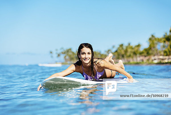 Attractive Young Woman Surfing in Hawaii  Paddling out to the Lineup