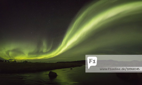 'Northern lights over a river and farm in Northeast Iceland; Iceland'