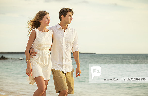 Young couple in love  Attractive man and woman enjoying romantic evening walk on the beach  Watching the sunset