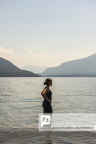 'A woman standing in Lake Maggiore; Ascona  Ticino  Switzerland'