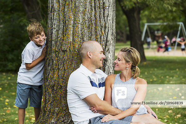 'A married couple spending quality time together in a park during a family outing with their son peeking from behind a tree; Edmonton  Alberta  Canada'