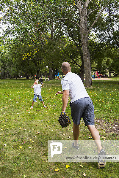 'Father and son playing baseball in a park; Edmonton  Alberta  Canada'