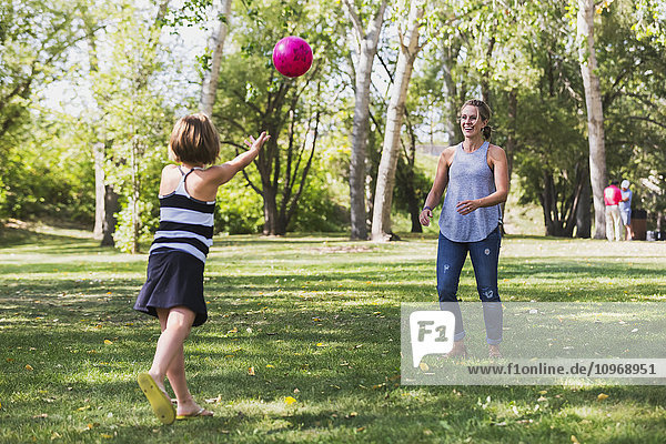 'Mother and daughter throwing a ball in a park during a family outing; Edmonton  Alberta  Canada'