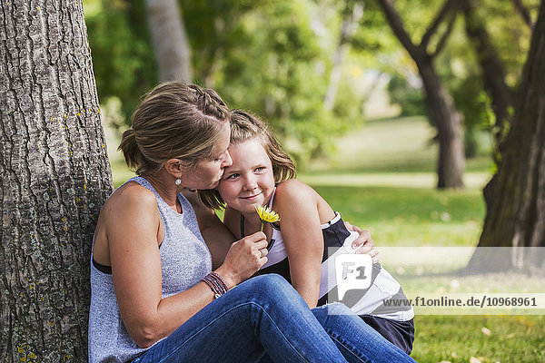 'Mother getting a flower from her daughter while spending quality time at a park during a family outing; Edmonton  Alberta  Canada'