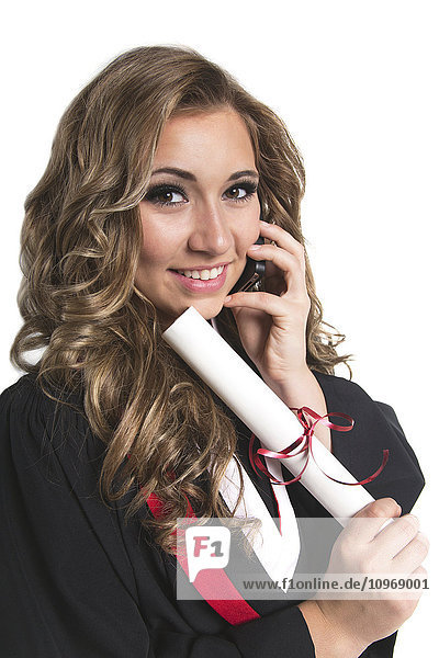 'Young female graduate holding her diploma and talking on her smart phone; Edmonton  Alberta  Canada'