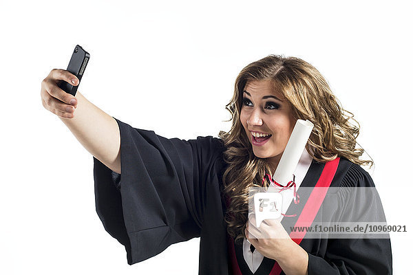 'Young graduating woman taking a self-portrait with her smart phone and celebrating her graduation; Edmonton  Alberta  Canada'