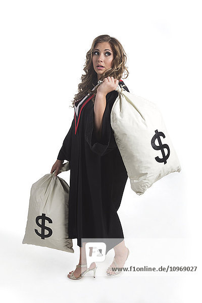 'Young graduating woman holding money bags to symbolize the costs of her education; Edmonton  Alberta  Canada'