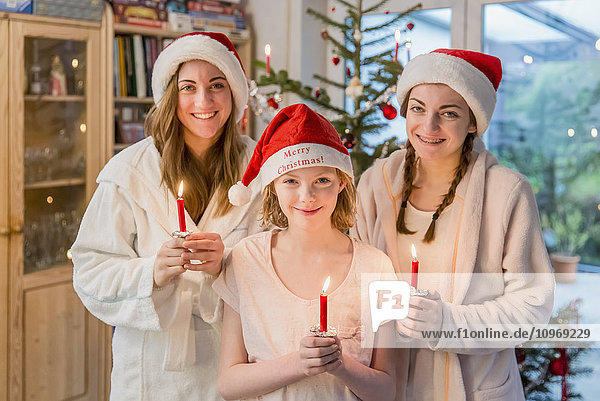 'Three sisters wearing santa hats and holding lit candles standing in front of a Christmas tree decorated with ornaments and tinsel; Bonn  Nordrhein Westfalen  Germany'