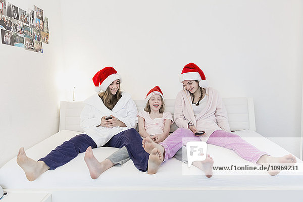 'Three sisters wearing santa hats  pajamas and robes and sitting together on a couch looking at two cell phones while smiling; Bonn  Nordrhein Westfalen  Germany'