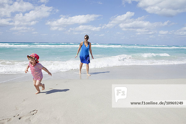 'Child running and crying on the beach with her mother; Varadero  Cuba'