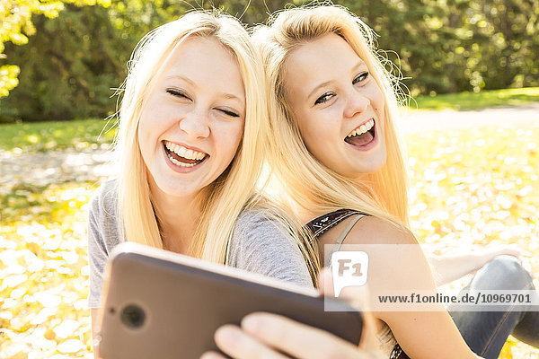 'Two sisters having fun outdoors in a city park in autumn and laughing at the selfies they have taken of themselves; Edmonton  Alberta  Canada'