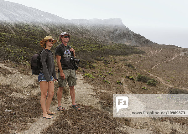 'A young couple stands on a rugged dirt trail on a mountainous landscape looking out; Praia da Cordoama  Portugal'