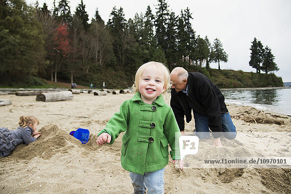 'A young girl walks towards the camera while a grandfather and granddaughter play in the background on the beach in winter at Stanley Park; Vancouver  British Columbia  Canada'