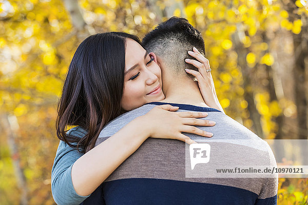'A young Asian woman hugging her boyfriend in a park in autumn and looking over his shoulder at the camera; Edmonton  Alberta  Canada'