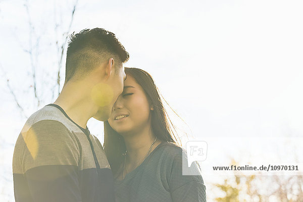 'A young Asian couple enjoying quality time together outdoors in a park in autumn and touching their foreheads together affectionately in the warmth of the sunlight during the early evening; Edmonton  Alberta  Canada'