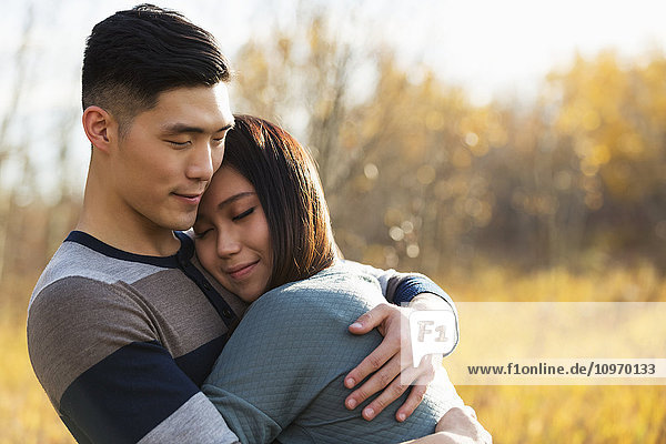 'A young Asian couple enjoying quality time together outdoors in a park in autumn and embracing each other in the warmth of the sunlight during the early evening; Edmonton  Alberta  Canada'