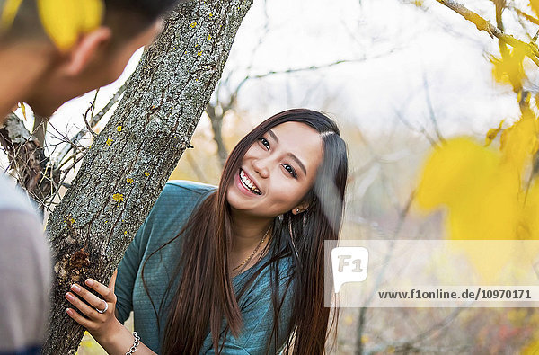 'A young Asian couple on a romantic date outdoors and playing hide and seek in a park during autumn; Edmonton  Alberta  Canada'