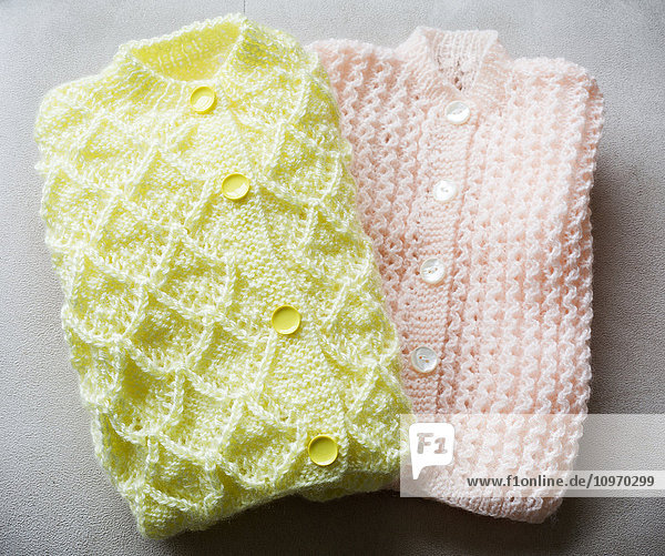 Handmade knit baby sweaters in pink and yellow on a grey background
