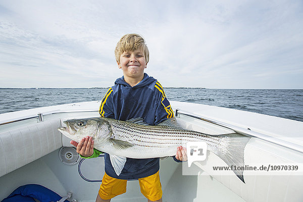 'A young boy holds a large Striped Bass on a fishing boat off the Atlantic coast; Boston  Massachusetts  United States of America'