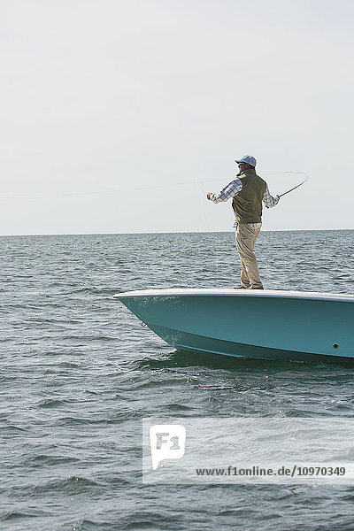 'A man stands casting his fishing line off the front of a boat on the Atlantic coast; Cape Cod  Massachusetts  United States of America'