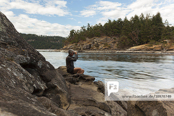 'A senior man watches the tides at Dodds Narrows on Vancouver Island; British Columbia  Canada'