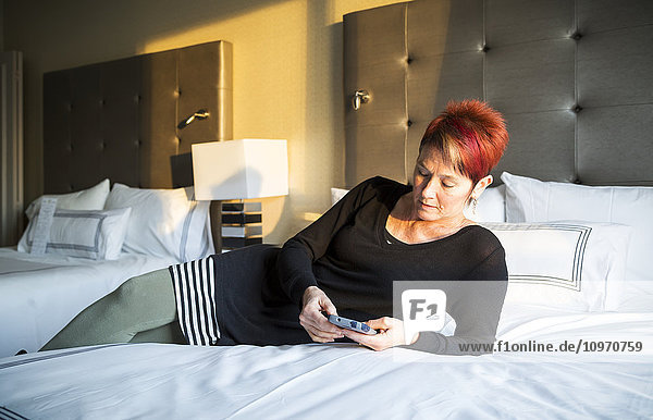 'A woman laying on a hotel bed and texting; Vancouver  British Columbia  Canada'