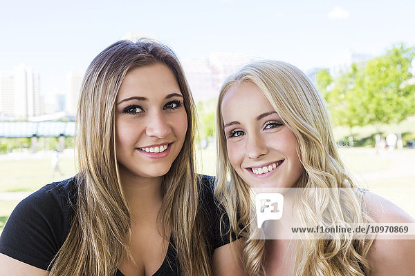 'Two girlfriends posing for the camera while enjoying the outdoors in a downtown city park; Edmonton  Alberta  Canada'
