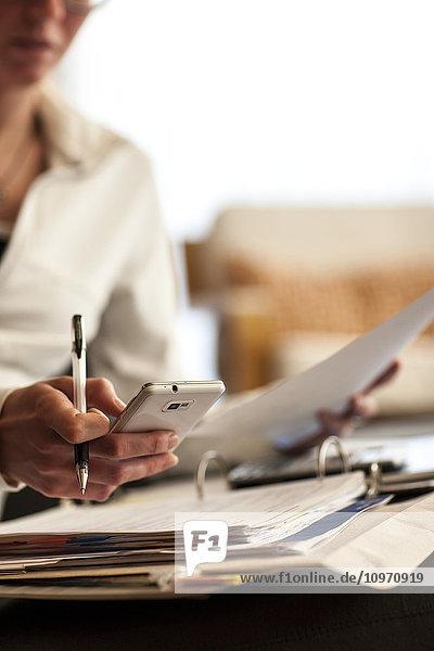 'A woman working at a desk filled with paperwork and a calculator; Regina  Saskatchewan  Canada'