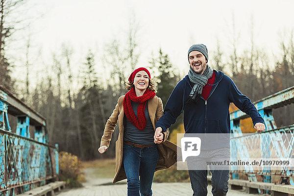 'A young couple running on a bridge in a city park in autumn; Edmonton  Alberta  Canada'