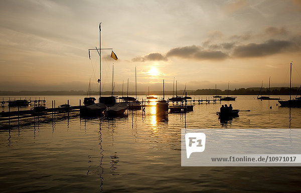 'The sun setting behind clouds and reflecting on the water in a tranquil harbour; Steinebach  Bavaria  Germany'