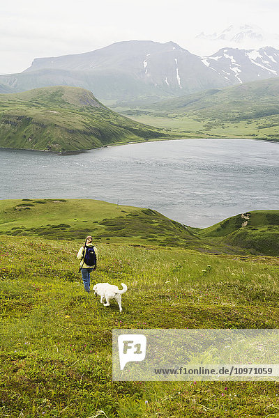 'A Woman Hiking With Her Dog And Enjoying The View Of Isanotski Strait In False Pass  From Unimak Island's Eastern Shore; Alaska  United States Of America'