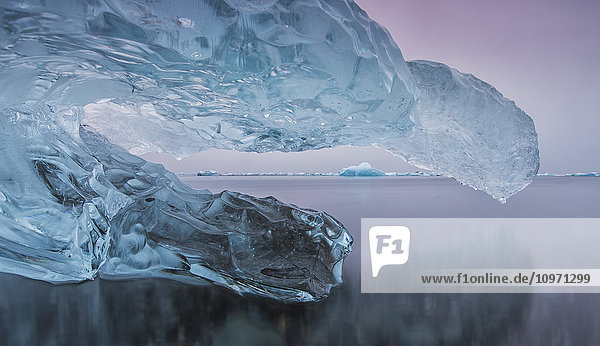 'Iceberg On The Beach Along The South Coast Of Iceland With A River Flowing By It Leading Towards The Ocean; Iceland'