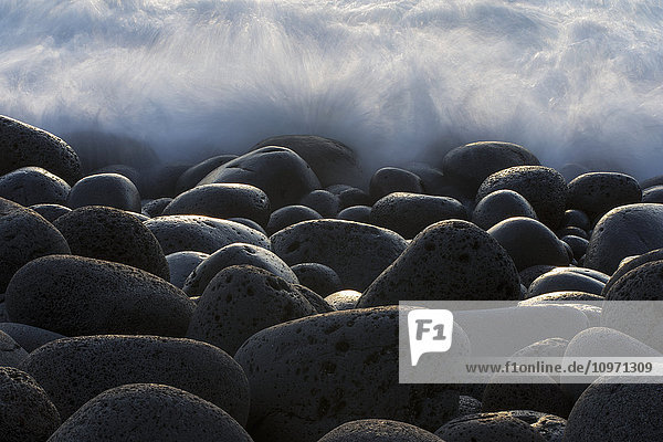 'Waves Crashing Over Round Rocks On The Southwestern Coast Of Iceland; Iceland'