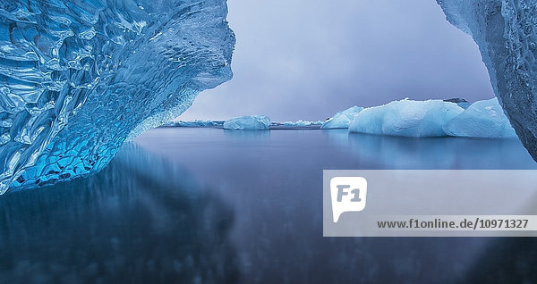 'Icebergs Reflected In Tranquil Water; Southern Iceland'