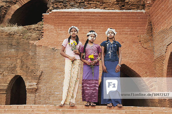 'Girls posing with flowers and face paint; Bagan  Myanmar'
