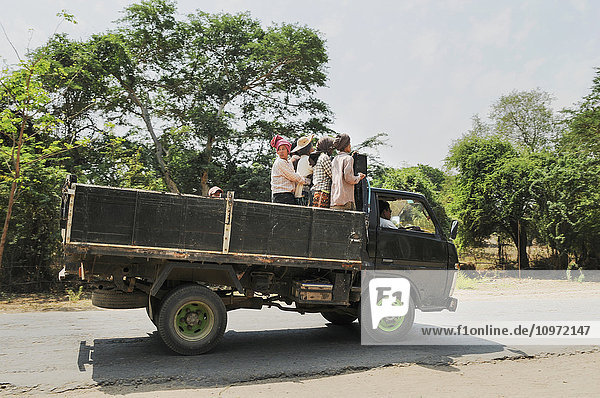 'Local workers riding in the back of the truck; Bagan  Myanmar'