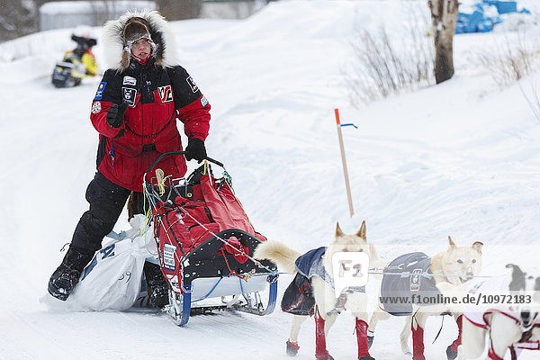 Aliy Zirkle moves to a parking spot dragging her food bags after checking in at the Ruby checkpoint during Iditarod 2015