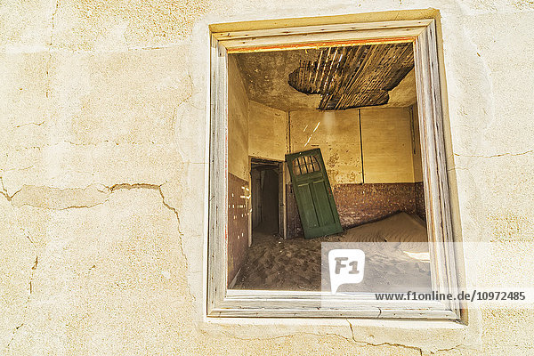 'Sand in the rooms of a colourful and abandoned house; Kolmanskop  Namibia'