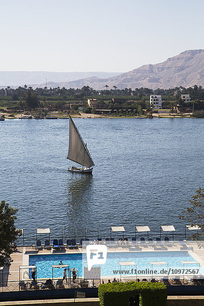'Hotel swimming pool (foreground)  Felucca on the Nile River; Luxor  Egypt'
