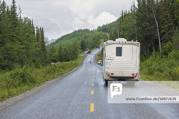 RV camper drives down the Alaska Highway  west of Fort Nelson  British Columbia Canada  Summer