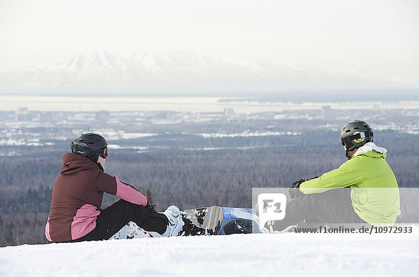 Couple strap on their snowboards at the top of Hilltop Ski Area in Anchorage  Alaska