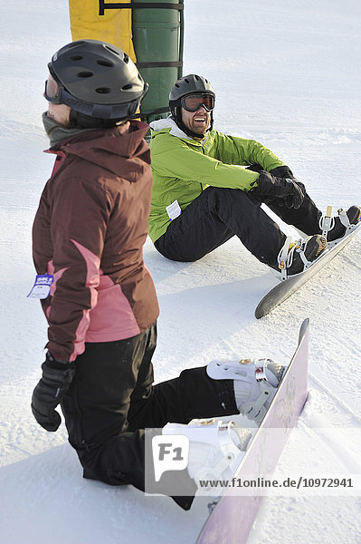 Couple relax while snowboarding at Hilltop Ski Area in Anchorage  Alaska