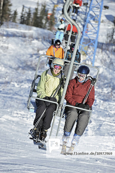 Friends ride the 3800-feet double chairlift at Mt. Aurora Skiland near Cleary Summit north of Fairbanks  Alaska.