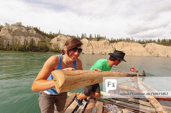 Two people steering a handmade raft down the Yukon River near Carmacks  Yukon Territory  Canada